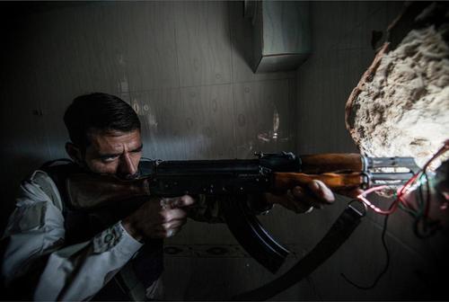 یکی از نیروهای مخالف بشار اسد در حال شلیک به سمت نیروهای دولتی از خانه ای درشهر حلب سوریه