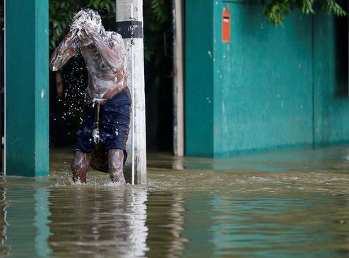 استحمام یک مرد در سیلاب شهر بیاگاما در سریلانکا
