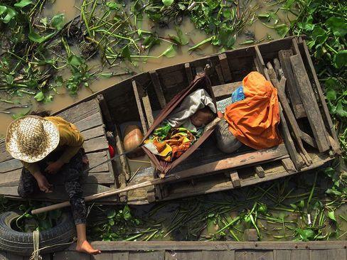 قایقی در کنار خانه های روی رودخانه در کامبوج