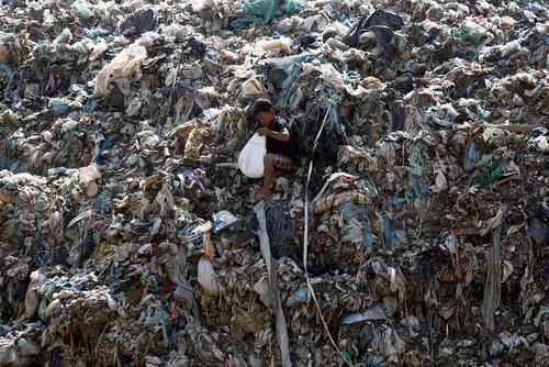یک کودک کامبوجی در حال جمع کردن اشیا از یک زباله دانی – شهر پنوم پن