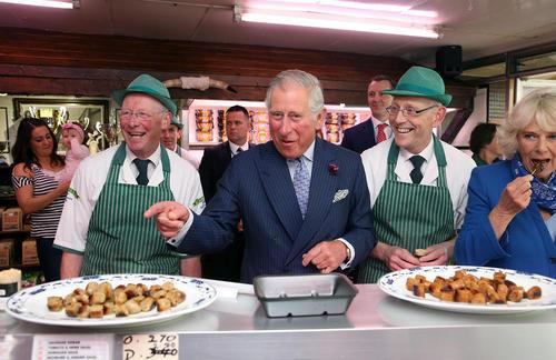 پرنس چارلز ولیعهد بریتانیا و همسرش در حال خوردن سوسیس در یک مغازه قصابی در شهر دونگال ایرلند