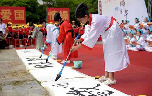 دانش آموزان چینی با لباس سنتی در حال خوش نویسی چینی – گینگژو