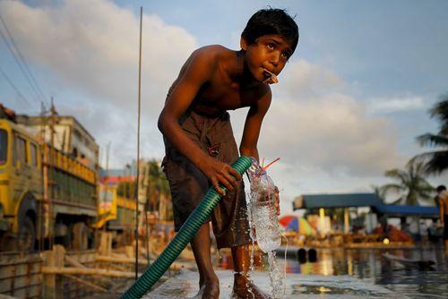 نوجوان بی سرپناه بنگلادشی در حال پر کردن یک بطری آب – داکا