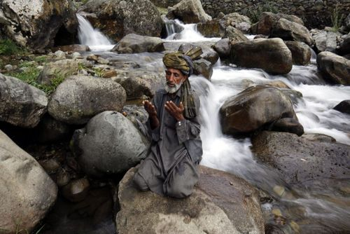 نماز خواندن مرد مسلمان کشمیری روی سنگ رودخانه – سرینگر