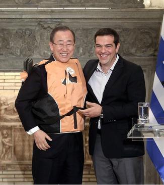 بستن جلیقه نجات پناهجویان به بان کی مون دبیر کل سازمان ملل در جریان دیدار او با الکسیس سیپراس نخست وزیر یونان در آتن. دبیر کل سازمان ملل به منظور بررسی وضعیت پناهجویان به یونان سفر کرده است