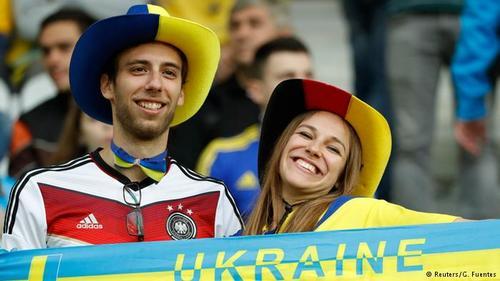 زوجی با دو ملیت متفاوت. مردی با پیراهن تیم ملی آلمان و کلاهی با رنگهای پرچم اوکراین و زنی با پیراهن تیم ملی اوکراین و کلاهی با رنگهای پرچم آلمان.