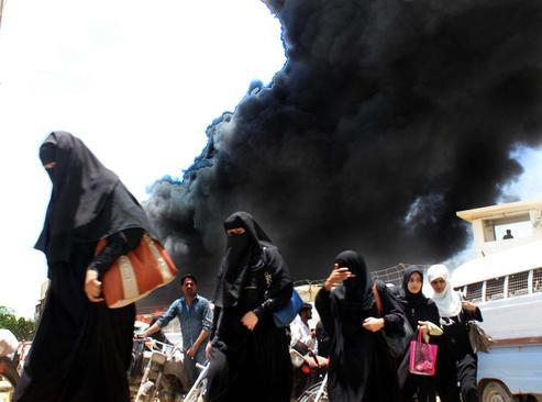 خروج کارگران یک کارخانه پارچه در کراچی پاکستان پس از آتش سوزی گسترده در آن