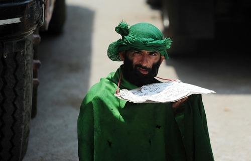 یک متکدی در بیرون مسجدی در شهر الله آباد هند