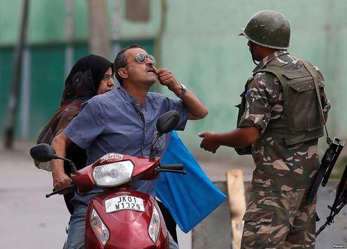 مردی در سرینگر کشمیر در حال نشان دادن دندان خود به پلیس است تا از محدودیت های ترافیکی عبور کرده و به دکتر برود
