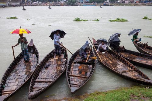 انتظار مسافربران قایقی در حاشیه رود بوریگانگا شهر داکا برای مشتری
