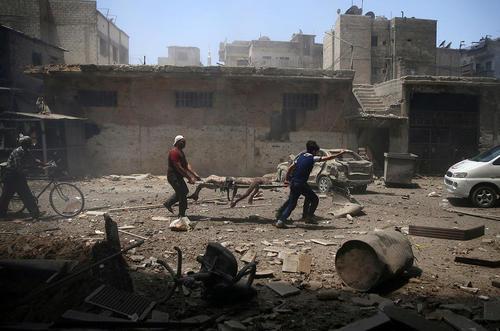 انتقال مجروحان و کشته ها از منطقه ای بمباران شده در شهر دوما در حومه دمشق