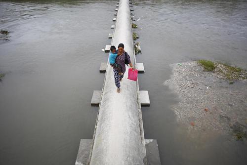 عبور یک مادر با فرزندش از پل سد دریاچه باگماتی در شهر کاتماندو نپال