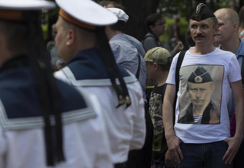 تی شرت با تصویر پوتین بر تن کهنه سرباز نیروی دریایی روسیه در جشن روز نیروی دریایی روسیه در شهر سن پترز بورگ