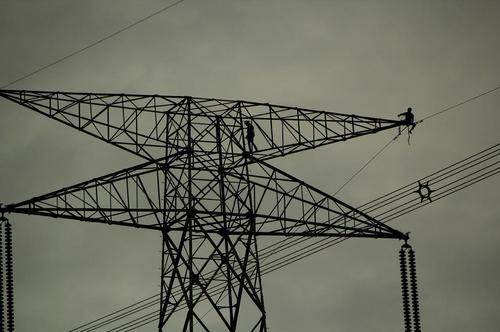 کارگران در حال کار روی دکل های بزرگ انتقال برق – هند