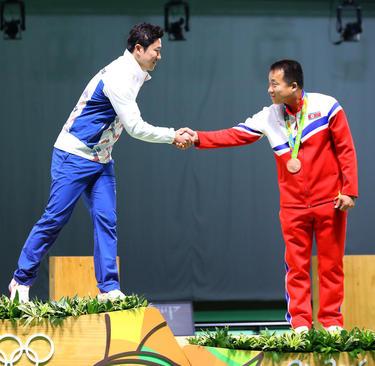 دو ورزشکار کره جنوبی و شمالی که در تیراندازی با تپانچه بادی در المپیک ریو مدال گرفته اند روی سکو در حال دست دادن هستند