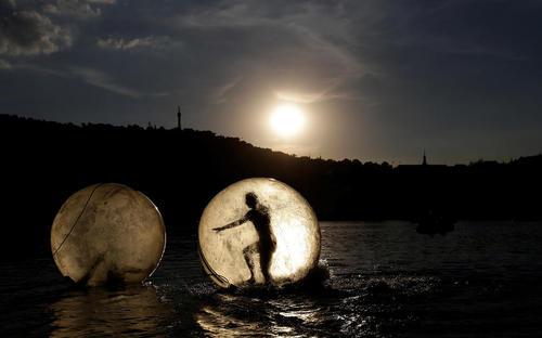 تفریح مردم در داخل توپ های بزرگ پلاستیکی در رودخانه ای در شهر پراگ