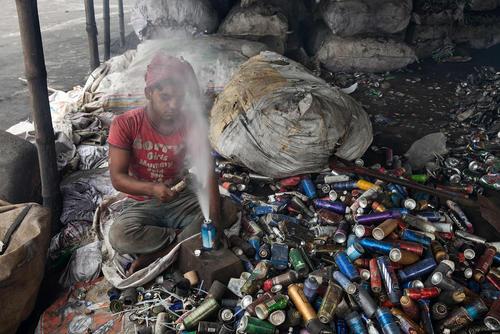 جوان بنگلادشی در حال سوا کردن قطعات آلومینیومی از زباله های صنعتی