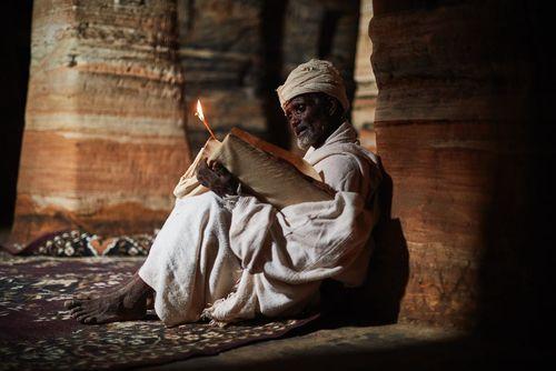 کشیش اتیوپیایی در کلیسایی قرن یازدهمی در حال خواندن دعا از انجیل