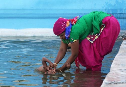 مادر هندو در حال آب تنی دادن فرزند خردسالش در روخانه معبد طلایی – آمریتسار