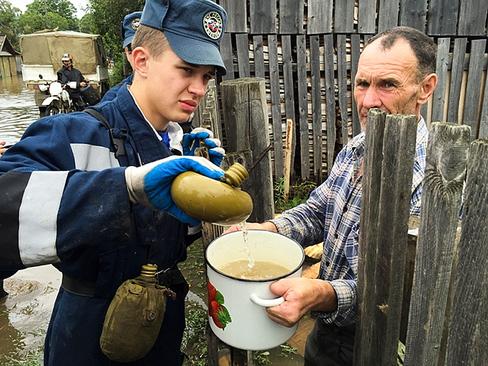 نیروی امدادی در حال ریختن آب آشامیدنی برای ساکنان منطقه ای سیلزده در روسیه