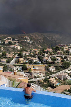 مردی در استخر ویلای خود در حال تماشای آتش سوزی جنگل های اسپانیا