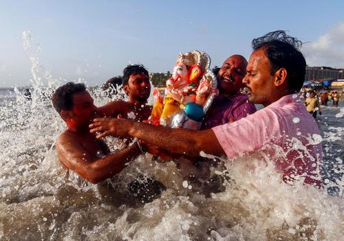 مجسمه خدای گانش در حال حمل به دریا از سوی هندوها در جریان جشنواره خدای گانش – ساحل بمبئی در اقیانوس هند
