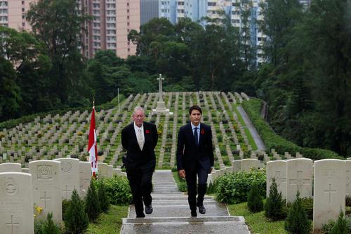 جاستین ترودو نخست وزیر کانادا به همراه یک مورخ انگلیسی در حال بازدید از آرامگاه سربازان کانادایی در هنگ کنگ است. این سربازان در جنگ دوم جهانی کشته شده اند
