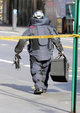پلیس نیویورک در حال حمل یک بسته مشکوک به بمب که از رستورانی در میدان تایمز کشف شده است