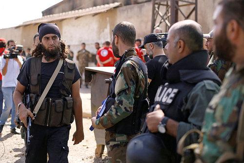 یک نیروی شورشی در حال عبور از مقابل نیروهای ارتش سوریه پس از توافقنامه محلی آتش بس  -شهر حمص