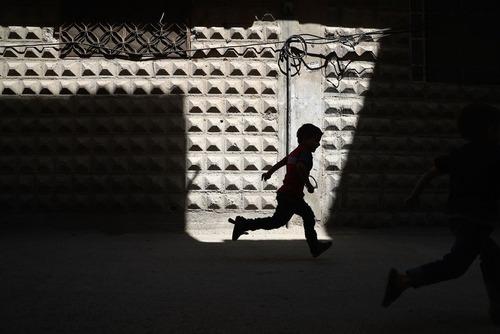 دویدن یک پسر بچه سوری در محله های تحت کنترل شورشیان در شهر دوما در حومه شرقی دمشق