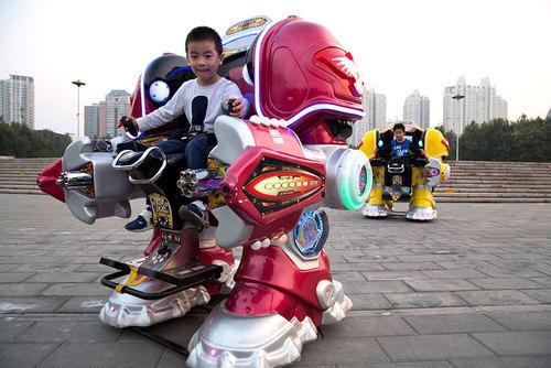 سوار شدن کودکان روی ماشین روبات بزرگ در پارکی در شهر پکن