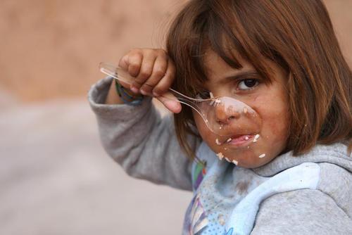 کودک گریخته از موصل عراق در یک کمپ در نزدیکی شهر اربیل و در حال غذا خوردن