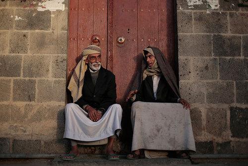 دو یمنی در مقابل خانه ای در صنعا نشسته اند