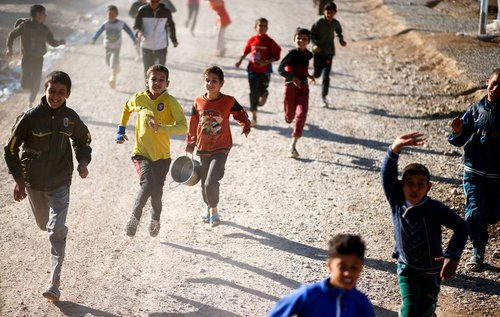 دویدن کودکان به دنبال ماشین توزیع غذا در اردوگاه آوارگان جنگی در عراق